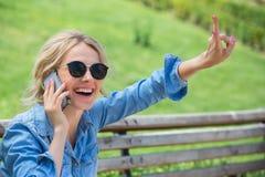 El hablar rubio lindo en un teléfono celular Imagen de archivo