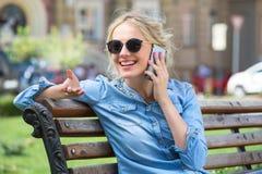 El hablar rubio lindo en un teléfono celular Imagen de archivo libre de regalías
