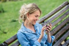 El hablar rubio lindo en un teléfono celular Imágenes de archivo libres de regalías