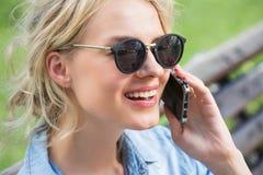 El hablar rubio lindo en un teléfono celular Foto de archivo