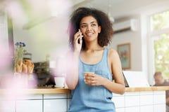 El hablar sonriente africano joven alegre hermoso de la estudiante en el café de consumición del teléfono en café Fotos de archivo libres de regalías