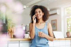 El hablar sonriente africano joven alegre hermoso de la estudiante en el café de consumición del teléfono en café Imagenes de archivo