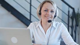 El hablar sonriente de cliente empresa de la mujer hermosa del servicio con una cámara en el centro de atención telefónica Fotos de archivo
