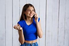 El hablar sonriente de la muchacha hermosa joven en el teléfono sobre el fondo de madera blanco Fotos de archivo