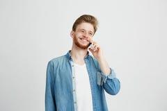 El hablar sonriente de risa feliz alegre del hombre joven en el teléfono sobre el fondo blanco Fotos de archivo