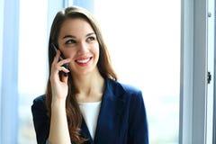 El hablar sonriente del teléfono de la mujer de negocios Fotos de archivo libres de regalías