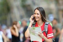 El hablar turístico adolescente en el teléfono que sostiene un mapa Foto de archivo libre de regalías