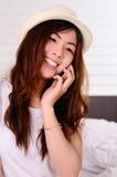 El hablar y charla adolescentes asiáticos con el teléfono móvil Imagenes de archivo