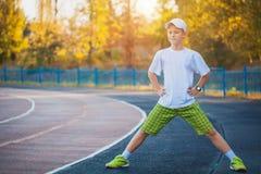 El hacer adolescente del muchacho se divierte ejercicios en un estadio Imagen de archivo libre de regalías