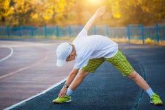 El hacer adolescente del muchacho se divierte ejercicios en un estadio Fotografía de archivo libre de regalías
