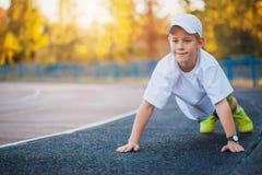 El hacer adolescente del muchacho se divierte ejercicios en un estadio Foto de archivo