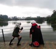 El hacer adolescente joven de los pares cosplay con el vestido negro y las pelucas blancas Traje del animado fotos de archivo libres de regalías
