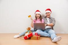 El hacer compras cariñoso joven hermoso de los pares en línea mientras que se sienta en el floore junto foto de archivo libre de regalías