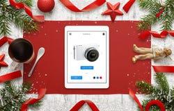El hacer compras con la tableta en sitio web del comercio electrónico Tiempo de la Navidad Foto de archivo