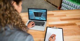 El hacer compras de la empresaria en línea mientras que escribe notas Fotos de archivo