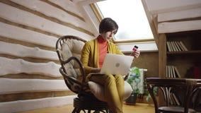 El hacer compras de la mujer en línea usando el ordenador portátil y la tarjeta de crédito metrajes