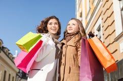 El hacer compras de los amigos. Opinión de ángulo bajo del standi feliz de dos mujeres jovenes Fotos de archivo libres de regalías