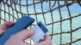 El hacer compras del hombre en línea con la tarjeta y el smartphone de crédito almacen de metraje de vídeo
