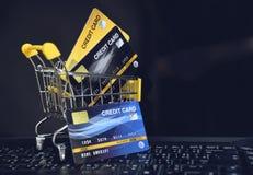 El hacer compras en línea con la tarjeta de crédito en un carro de la compra en el fondo del ordenador portátil para el pago en l fotos de archivo