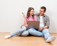 El hacer compras en línea junto El hacer compras cariñoso joven hermoso de los pares en línea mientras que se sienta en el floore fotos de archivo