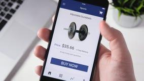 El hacer compras en línea usando el smartphone app y elegir el equipo de deporte almacen de metraje de vídeo