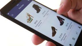 El hacer compras en línea usando el smartphone app y elegir los zapatos almacen de metraje de vídeo