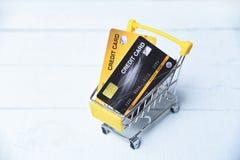 El hacer compras en l?nea con la tarjeta de cr?dito en un carro de la compra en el fondo de madera para el pago en l?nea en casa imagen de archivo