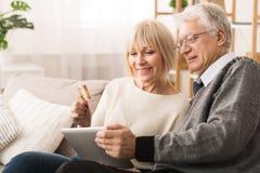 El hacer compras en l?nea Los ancianos se juntan usando la tableta y la tarjeta de cr?dito foto de archivo