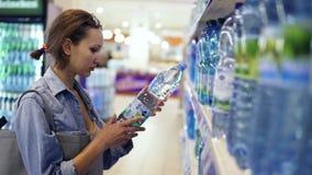 El hacer compras en tienda Mujer bonita joven que selecciona la botella de agua Assorment grande del agua en la fila, vista later almacen de video