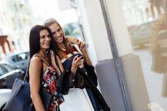 El hacer compras hermoso de dos mujeres fotos de archivo