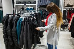 El hacer compras, moda, venta, estilo y concepto de la gente - mujer joven en capa gris y la bufanda roja que eligen la chaqueta  Fotografía de archivo