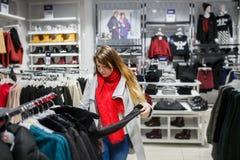 El hacer compras, moda, venta, estilo y concepto de la gente - mujer joven en capa gris y la bufanda roja que eligen la chaqueta  Foto de archivo libre de regalías