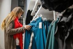 El hacer compras, moda, venta, estilo y concepto de la gente - mujer joven en capa gris y la bufanda roja que eligen los pantalon Fotos de archivo libres de regalías