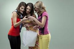 El hacer compras sonriente de los altos talones de las mujeres jovenes Imagen de archivo libre de regalías