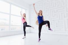 El hacer de dos mujeres jovenes ejercicios cardiios Foto de archivo libre de regalías