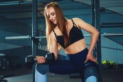 El hacer de la muchacha del gimnasta exersizes con pesa de gimnasia fotos de archivo