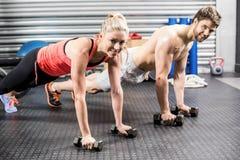 El hacer de los pares empuja hacia arriba con pesas de gimnasia Imagen de archivo