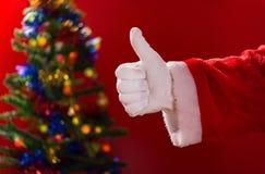 El hacer de Santa Claus pulgares encima del gesto con la parte posterior adornada del árbol de navidad encendido Foto de archivo