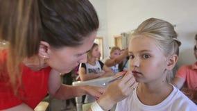 El hacer de Stylist del artista de maquillaje compone en el estudio para la muchacha del adolescente almacen de metraje de vídeo