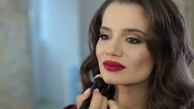El hacer del artista de maquillaje compensa a la muchacha hermosa en el salón, concepto de la belleza almacen de metraje de vídeo