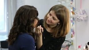 El hacer del artista de maquillaje compensa a la novia hermosa joven que aplica maquillaje de la boda almacen de metraje de vídeo
