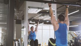 El hacer del atleta del hombre joven levanta ejercicio abdominal de la barra en gimnasio Fotografía de archivo