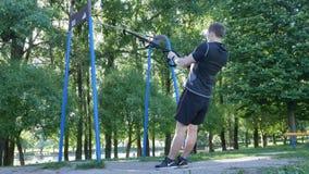 El hacer del comienzo del hombre levanta el ejercicio en lazos de la aptitud en parque del verano cantidad de la cámara lenta 4k almacen de metraje de vídeo