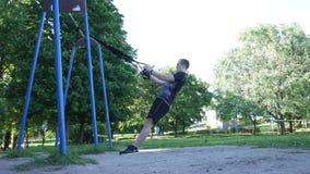 El hacer del hombre intenso levanta el ejercicio en lazos de la aptitud en parque ventoso del verano cantidad de la cámara lenta  metrajes
