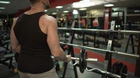 El hacer deportivo del individuo vario elevación-UPS con la barra del rizo, poniéndolo detrás en soporte en gimnasio metrajes