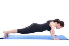 El hacer deportivo joven de la mujer empuja hacia arriba el ejercicio aislado en blanco Imagenes de archivo
