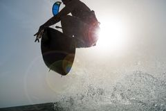 El hacer excursionismo de una persona que practica surf que salta en la puesta del sol Fotografía de archivo