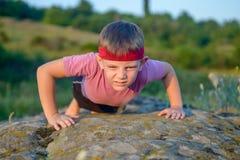 El hacer masculino fuerte del niño empuja hacia arriba en roca grande Fotos de archivo