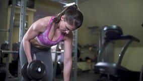 El hacer moreno hermoso de la mujer empujó pesas de gimnasia en el deltoideo de la parte posterior de la cuesta Parte posterior d almacen de video