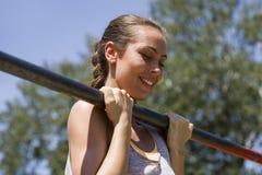 El hacer moreno joven de la mujer levanta en una barra horizontal a de los deportes Foto de archivo